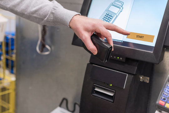 Man paying at the self-service counter using the touchscreen display and credit card. Isometric self-service cashier or terminal.