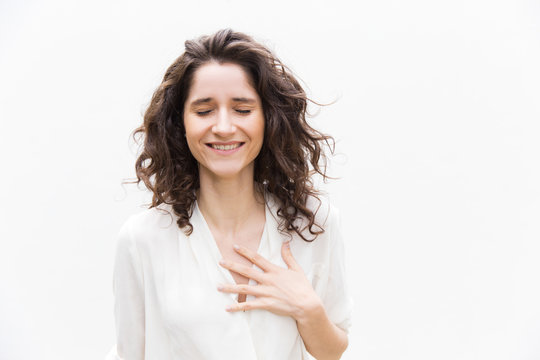 Happy grateful pretty woman with closed eyes applying hand to chest. Wavy haired young woman in casual shirt standing isolated over white background. Relief or gratitude concept