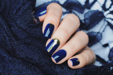 Fotobehang Manicure Deep blue manicure with gold design elements stripes and triangle. Blue lace background