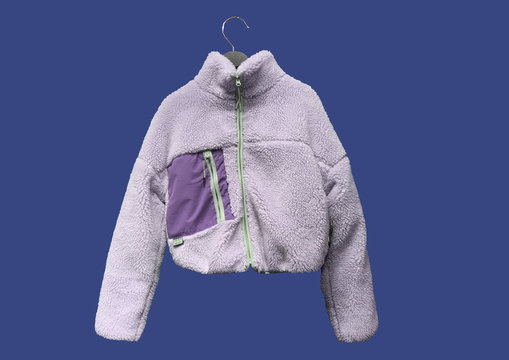 Purple faux suede and faux shearling jacket with contrasting details on hanger isolated on blue background. Composition of clothes. Ladies' Trench Coat. Winter clothes pattern.