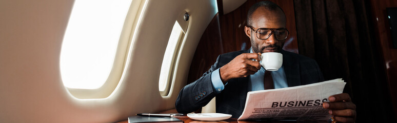 panoramic shot of african american businessman in glasses reading business newspaper while holding cup in private plane