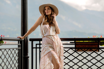 Sexy woman in summer dress relaxing outdoor over mountain background