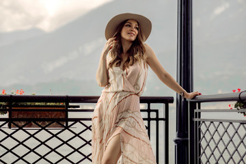 Fashionable woman in summer dress relaxing over mountain background