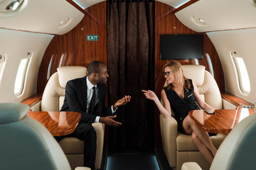 selective focus of happy african american businessman gesturing near businesswoman in private plane