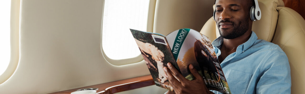 panoramic shot of african american man in wireless headphones reading magazine in private plane