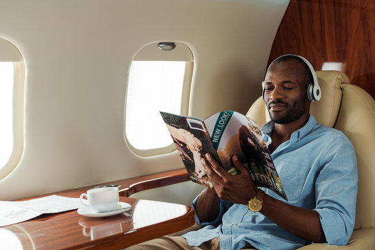 selective focus of african american man in wireless headphones reading magazine in private plane