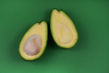 Avocado stock photo. Halved avocado stock images. Avocado isolated on a green background