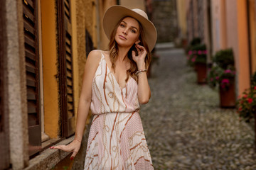 Beautiful young sexy woman in summer dress relaxing on vacation in italy