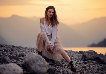 Fashionable female model in stylish outfit posing over mountain view