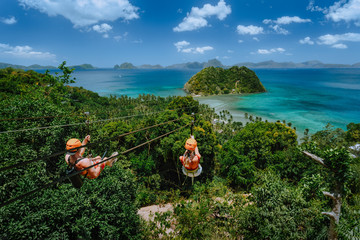 Zipline over Las Cabanas Beach with tourist on sunny day with white clouds over sea. El Nido, Palawan, Philippines
