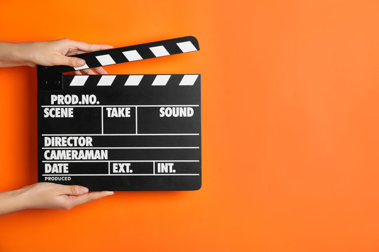 Woman holding clapperboard on orange background, closeup with space for text. Cinema production