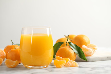 Glass of fresh tangerine juice and fruits on marble table