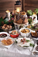 Christmas Eve table with traditional dishes and cakes