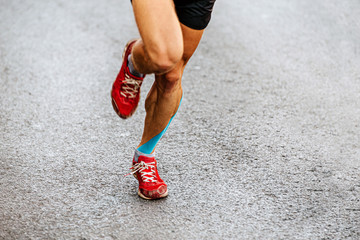 Fototapete - legs male runner with blue kinesio tape run on asphalt