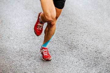 Wall Mural - legs male runner with blue kinesio tape run on asphalt