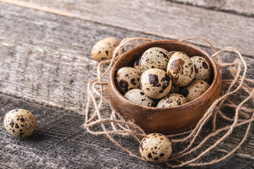 Quail eggs in wooden bowl.