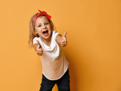 Active happy screaming kid girl in white t-shirt and red headband is showing thumbs up gesture on yellow