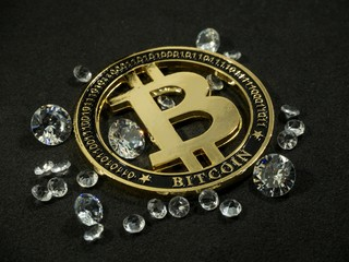 Shiny gold bitcoin virtual currency coin laying on black table with diamonds
