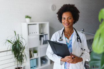 Portrait of female African American doctor standing in her office at clinic Fototapete