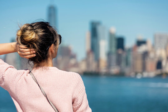 Woman in pink sweater posing on the background of New York city