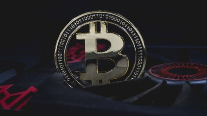 Shiny gold bitcoin coin crypto currency stuck in gpu graphic card cooling fan