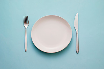 Clean empty white plate with knife and fork