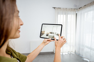 Young woman placing new furniture on a digital tablet into the empty interior, looking how it looks before buying. Concept of augmented reality in design and retail business