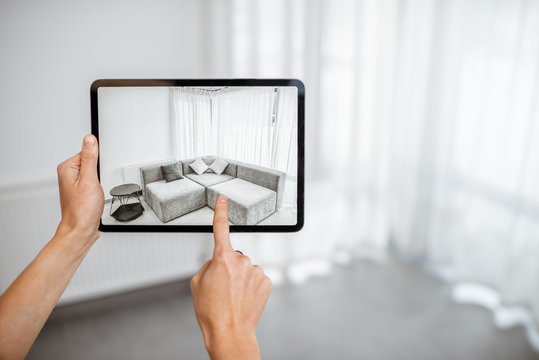 Placing new furniture on a digital tablet into the empty interior, looking how it looks before buying. Concept of augmented reality in design and retail business
