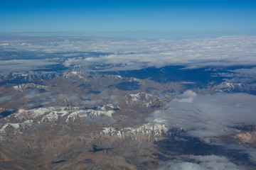 Aerial view above snow mountain peaks