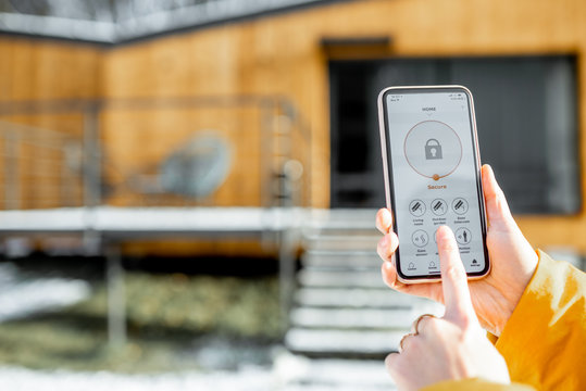 Holding phone with launched alarm app on the house background outdoors. Concept of controlling and managing home security from a mobile device