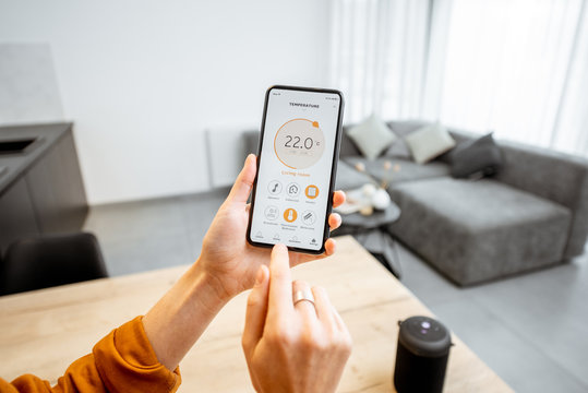 Controlling home heating temperature with a smart home, close-up on phone. Concept of a smart home and mobile application for managing smart devices at home