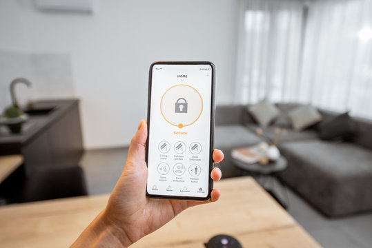 Holding a smartphone with launched security program indoors. Concept of controlling and managing home security from a mobile device