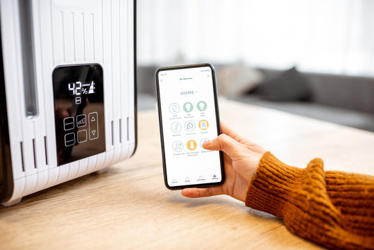 Close-up on a smart phone with launched home assistant application, controlling air humidifier at home