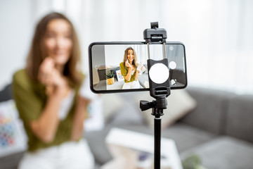 Young woman recording her vlog about healthy eating and nutritional supplements, close-up on a...