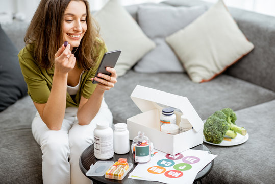 Woman taking nutritional supplements in the form of pills while sitting with smart phone at home. Concept of individual online selection of food supplements. Preventive medicine