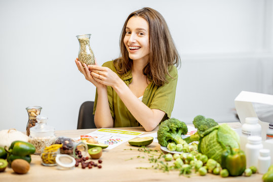 Portrait of a young cheerful woman with hemp seeds and lots of healthy green food on the table. Concept of food marijuana and well-being