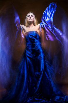 Young charming woman goddess in a blue dress