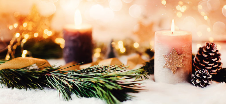 Romantic winter and christmas greeting card with text - Burning candle with natural fir and pine cone decoration on a bright background and copy space