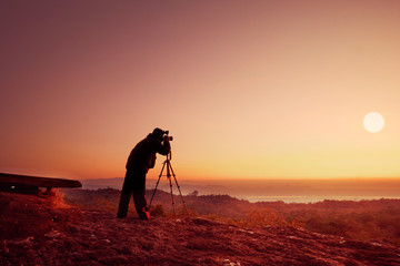 silhouette photographer take photo with sunset or sunrise background