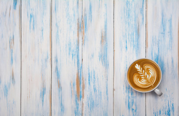 A cup of coffee on wooden table. Top view of coffee latte art with copy space. Drink and art concept.