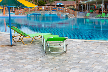 two sun loungers and an umbrella by the pool in a recreation area of the Spanish city of Magaluf
