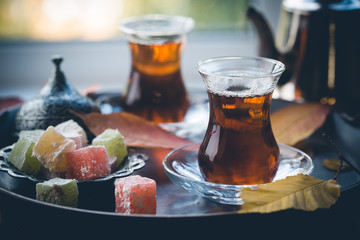 Glass Cup of turkish tea served in traditional style with summer outdore view