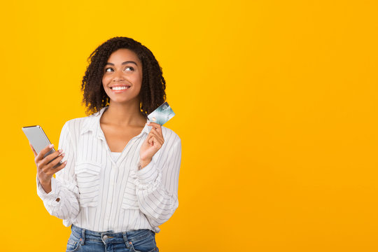 African american girl holding credit card and smartphone
