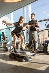Woman training with personal fitness instructor trainer in modern gym with equipment