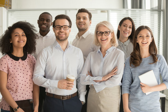 Smiling diverse employees posing for photo in office