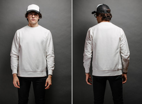 Man wearing blank white sweatshirt and empty baseball cap standing over gray background. Sweatshirt or hoodie for mock up, logo designs or design print with with free space.