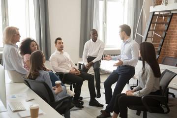 Obraz Multiethnic colleagues talk negotiating at informal office meeting - fototapety do salonu