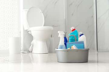 Cleaning supplies near toilet bowl in modern bathroom. Space for text