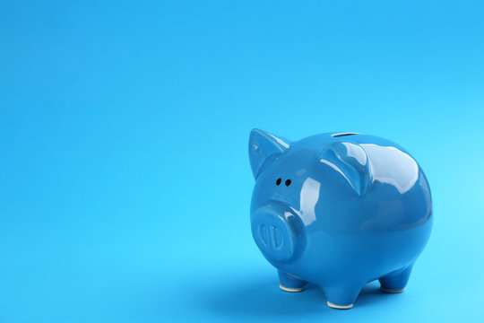 Piggy bank on blue background. Space for text