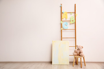Teddy bear on chair and decorative ladder near wall in child room. Space for text